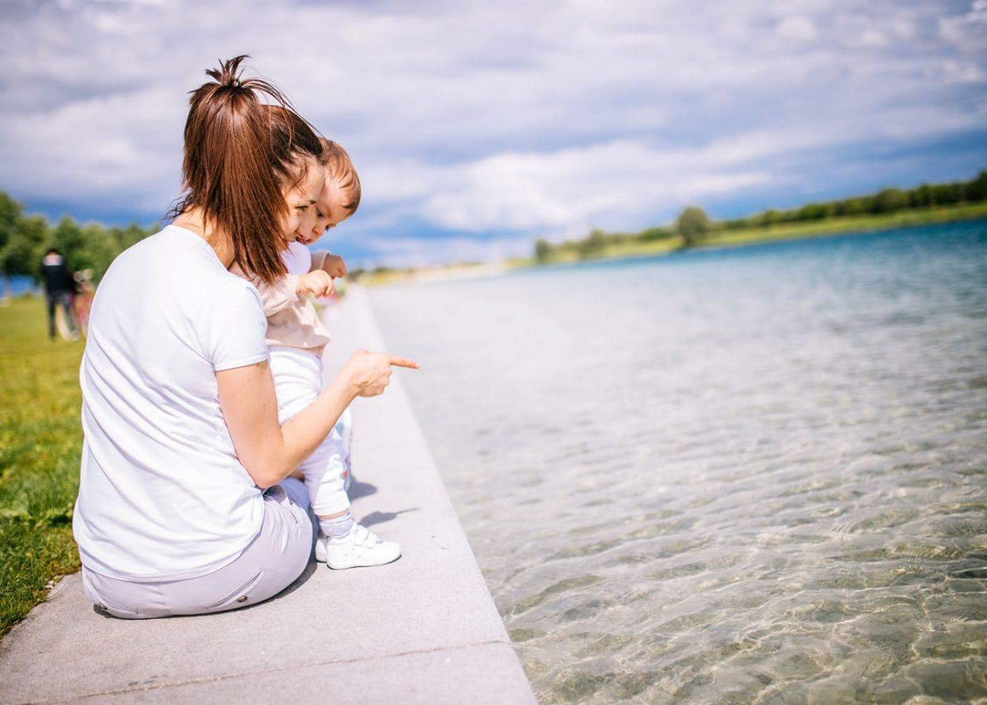 moeder met kind aan rand van het water